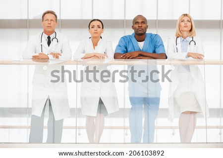 Confident team of medical experts. Low angle view of four confident doctors standing close to each other and looking away while leaning at the handrail - stock photo