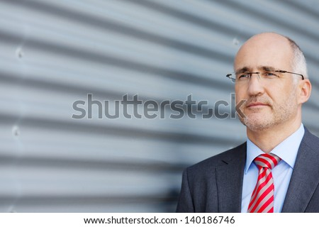Confident thinking mature businessman looking away by shutter - stock photo