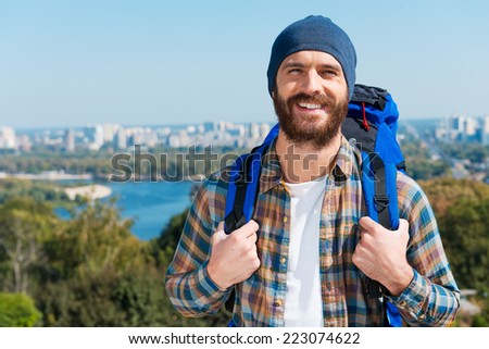 Confident tourist.  Handsome young man carrying backpack and looking at camera through the shoulders a with smile