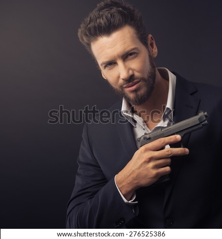 Confident undercover agent with a gun against dark background