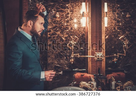 Confident well-dressed man combing hair in luxury bathroom interior. - stock photo
