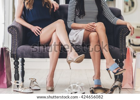 Confident with their choice. Part of young women with perfect legs keeping their legs crossed at knee while sitting on sofa at the shoe store - stock photo