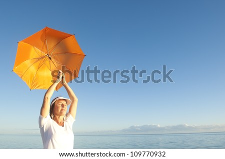 Confident woman in white shirt and pants standing with orange umbrella at peaceful ocean at Shark Bay, Western Australia, isolated with sea and blue sunset sky as background and copy space.
