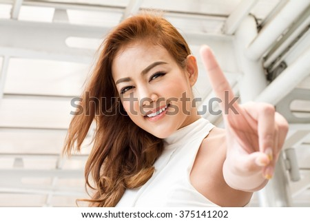 confident woman pointing one finger up - stock photo