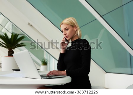 Confident woman talking on mobile phone and reading required information on portable net-book,female secretary calling to her boss to tell what she read about new project in network on laptop computer - stock photo