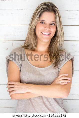 Confident woman with arms crossed and smiling - stock photo