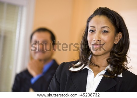 Confident young African-American businesswoman with middle-aged Hispanic male co-worker in background - stock photo