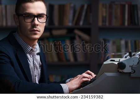 Confident young author. Side view of confident young author sitting at the typewriter and looking at camera with bookshelf in the background  - stock photo