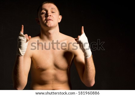 Confident young boxer gesturing his optimism with his gloved hands raising his finger in the air as he psyches himself up for a fight - stock photo