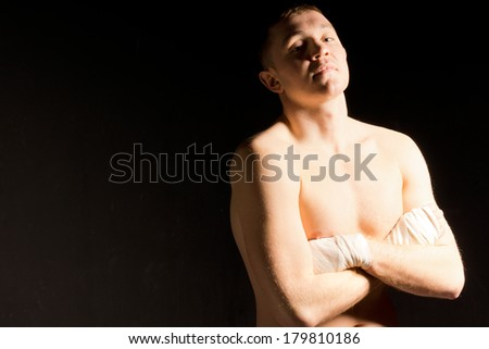 Confident young boxer waiting for his bout standing with folded arms and a supercilious look against a dark background with copyspace - stock photo