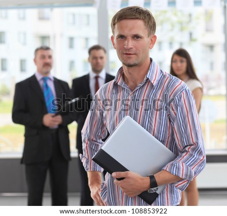Confident young business executive with his team in the background
