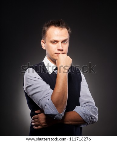 confident young business man on dark background
