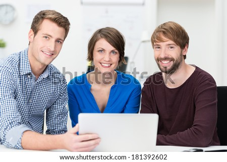 Confident young business team of two men and a woman grouped around a laptop as they sit at a desk in the office together smiling at the camera - stock photo