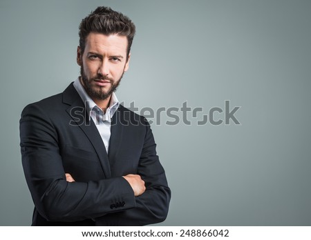 Confident young businessman posing on gray background - stock photo