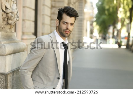 Confident young businessman standing on street.  Business people.