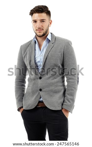 Confident young businessman standing with his hands in his pockets - stock photo