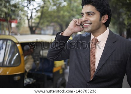 Confident young businessman using cell phone on city street - stock photo