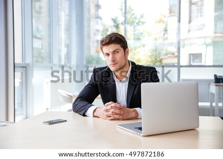 Confident young businessman with laptop and cell phone sitting at the table in office