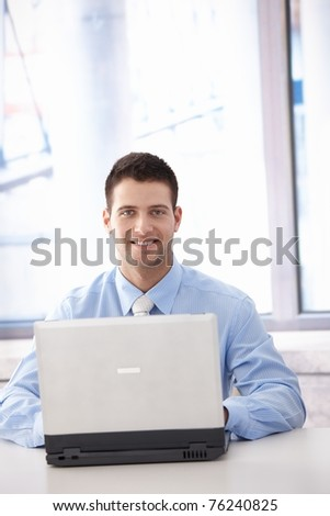 Confident young businessman working on laptop in bright office, smiling.?