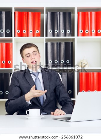 confident young businessman working on laptop in his office - stock photo
