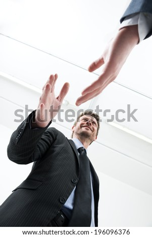 Confident young businessmen smiling and shaking hands bottom view. - stock photo