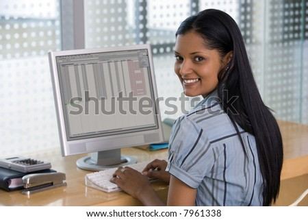 Confident young businesswoman at computer