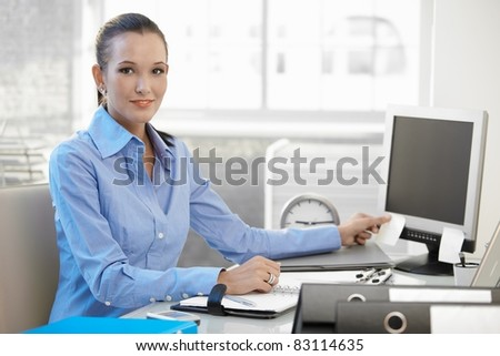 Confident young businesswoman at work, sitting at desk, looking at camera, smiling.?