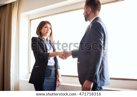 Confident young businesswoman greeting a client into her office and giving him a handshake