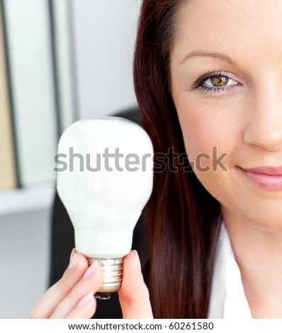 Confident young businesswoman holding a light bulb looking at the camera in her office - stock photo