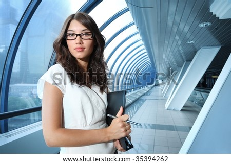 Confident young businesswoman in futuristic interior. - stock photo