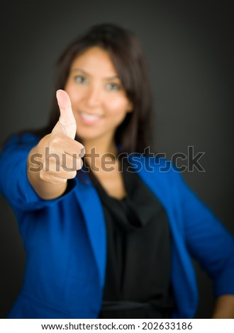 Confident young businesswoman showing thumb up sign