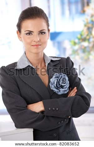 Confident young businesswoman standing arms crossed in office.? - stock photo