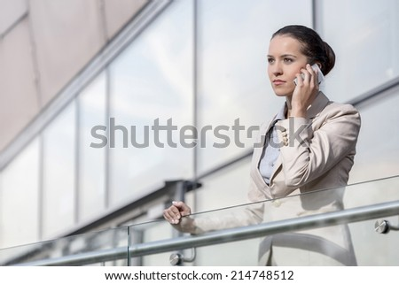 Confident young businesswoman using smart phone at office railing - stock photo
