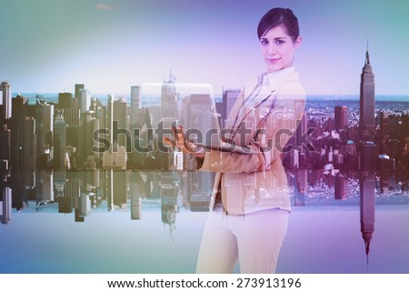 Confident young businesswoman with laptop against mirror image of city skyline - stock photo