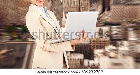 Confident young businesswoman with laptop against new york - stock photo