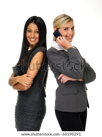 Confident young businesswomen stand together and look towards camera - stock photo