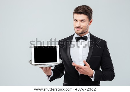 Confident young butler in tuxedo holding and pointing at blank screen tablet on tray - stock photo