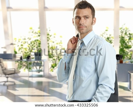 Confident young caucasian handsome businessman standing at bright office. Suit and tie. - stock photo