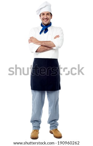 Confident young chef in white uniform and hat - stock photo