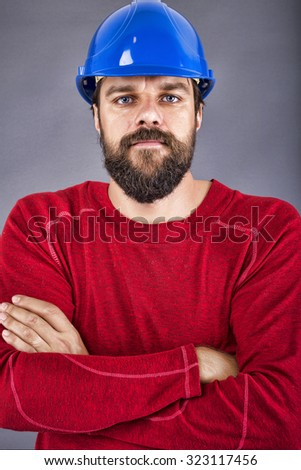 Confident young construction worker with hardhat and arms folded over gray background - stock photo