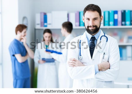 Confident young doctor posing in the office, he is smiling at camera with arms crossed, medical team on the background - stock photo