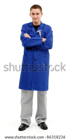 Confident young engineer standing with arms folded and looking. Caliper on his upper pocket - stock photo