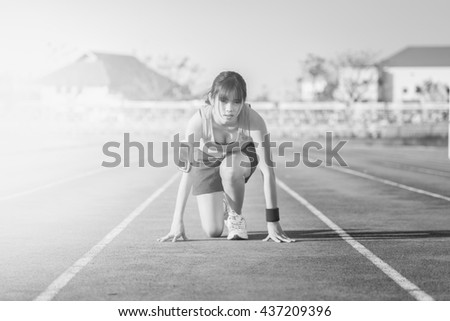 Confident young female athlete in starting position ready to start a sprint. Woman sprinter ready for a run. Woman running on a running track. running shoes. Woman running and jogging concept.  - stock photo
