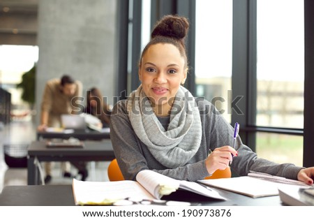 Confident young female student studying. Woman sitting at desk with books. - stock photo