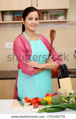 Confident young Indian woman with kitchen utensil  - stock photo