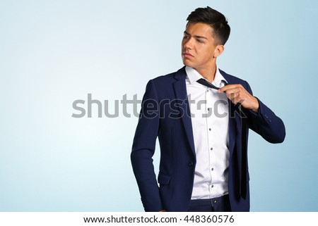 Confident young man adjusting his necktie
