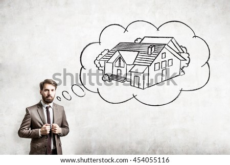 Confident young man daydreaming about buying a house on concrete background. Concept of mortgage and real estate