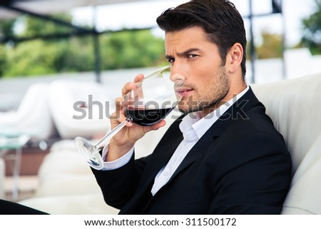 Confident young man drinking wine in restaurant