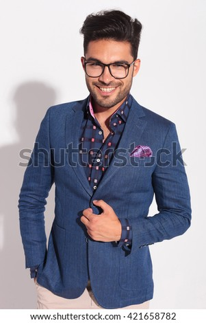 confident young man in suit laughing in studio while holding coat's button  - stock photo