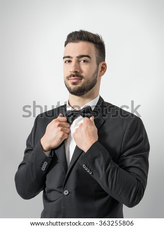 Confident young man in tuxedo with bow tie posing at camera holding suit collar. Desaturated portrait over gray studio background with retro vignette.